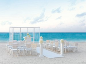 Beachfront wedding setting, with white chairs, and daisys