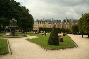 Fountain, grass and buildings at Place des Vosges, Paris